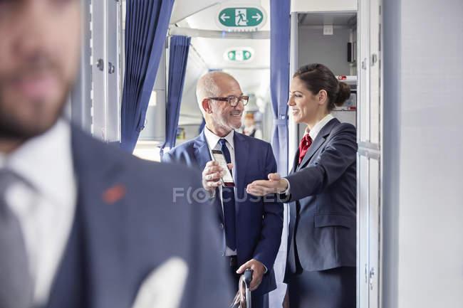Auxiliar de vuelo ayudando a empresario con digital tarjeta de embarque en el avión - foto de stock