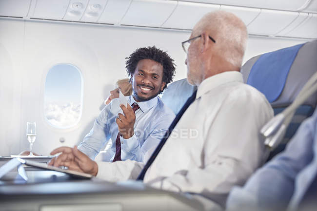 Smiling businessmen exchanging business cards on airplane — Stock Photo