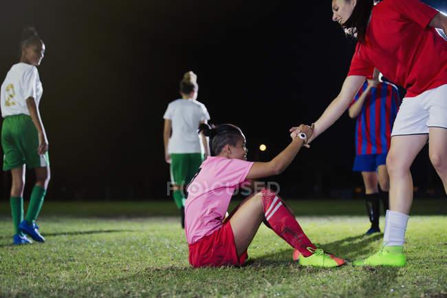 Молодая футболистка помогает павшему товарищу по команде встать на поле ночью — стоковое фото