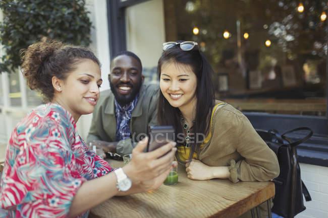 Юные друзья с помощью сотового телефона на тротуаре кафе — стоковое фото
