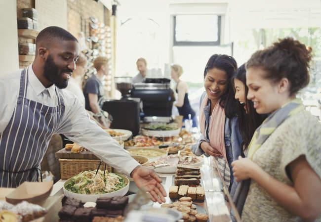 Travailleur de sexe masculin aider la clientèle féminine au café — Photo de stock