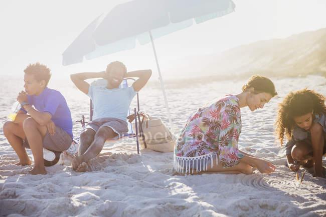 Famiglia multietnica che si rilassa e gioca nella sabbia sulla soleggiata spiaggia estiva — Foto stock