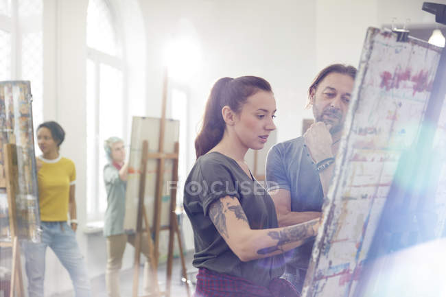 Focused artists painting at easel in art class studio — Stock Photo