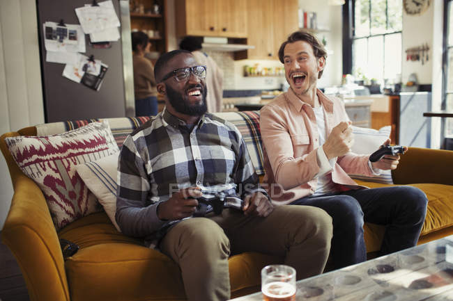Laughing men friends playing video game on living room sofa — Stock Photo