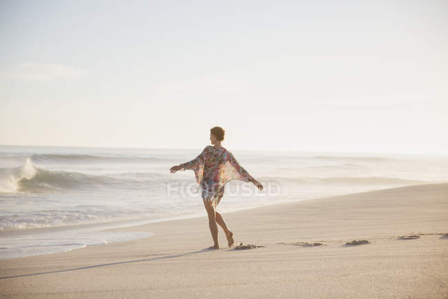 Carefree woman walking with arms outstretched on sunny summer ocean beach — Stock Photo