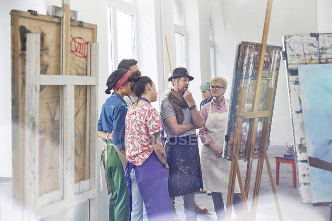 Art students and instructor examining, critiquing painting in art class studio — Stock Photo