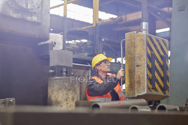 Male worker operating machinery in factory — Stock Photo