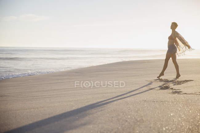 Carefree woman walking on sunny summer ocean beach — Stock Photo