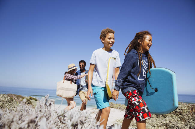 Family walking with boogie boards on sunny summer beach path — Stock Photo