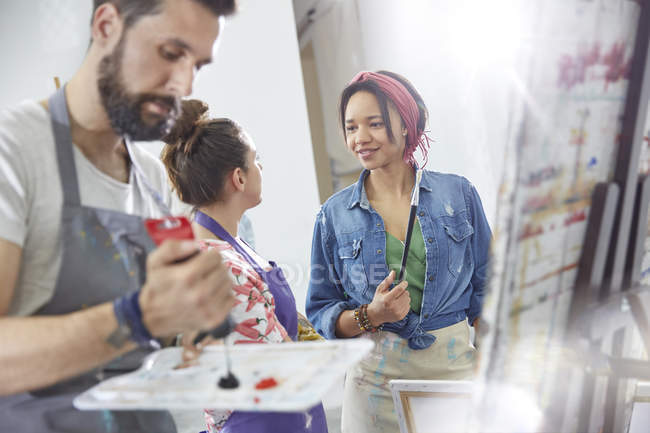 Artists talking and painting in art class studio — Stock Photo
