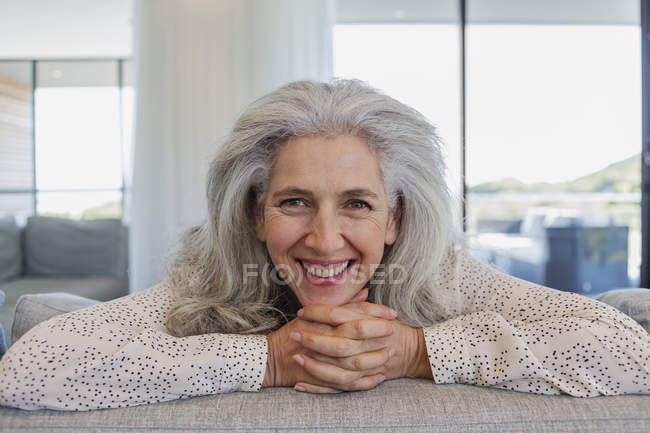 Portrait happy mature woman leaning over sofa in living room — Stock Photo