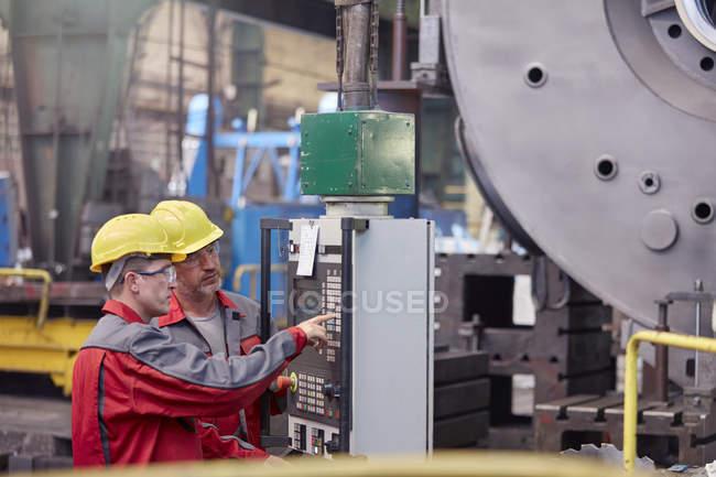 Männliche Arbeiter, die Bedienung von Maschinen am Bedienfeld in Fabrik — Stockfoto