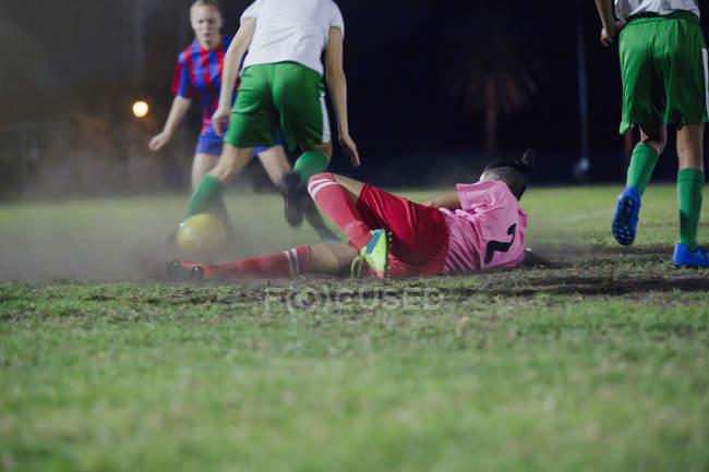 Junge Fußballerin stürzt und tritt den Ball beim Fußballspielen auf dem Feld in der Nacht — Stockfoto