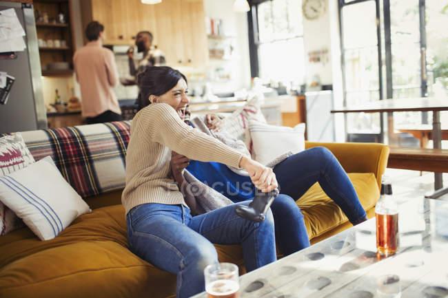 Игривая женщина играет в видеоигры на диване в гостиной — стоковое фото