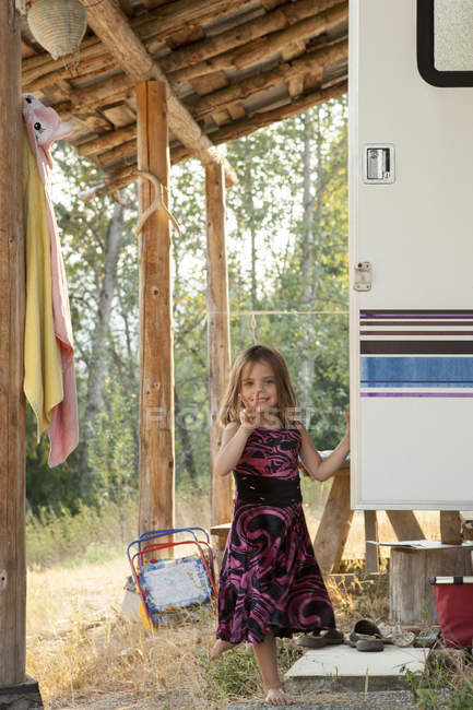 Portrait smiling, confident girl in dress gesturing peace sign outside rural camper — Stock Photo