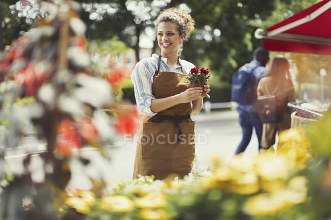 Smiling female florist working at flower shop storefront — Stock Photo