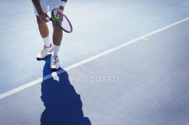 Молодой теннисист готовится подавать мяч на солнечно-синем теннисном корте — стоковое фото