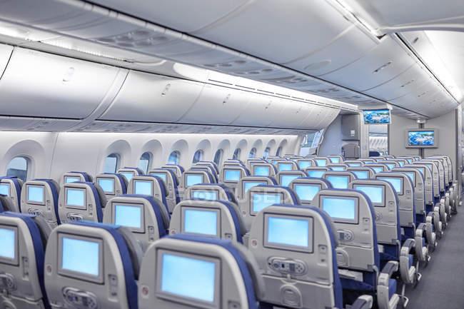 Ряды сидений с развлекательными экранами в самолете — стоковое фото
