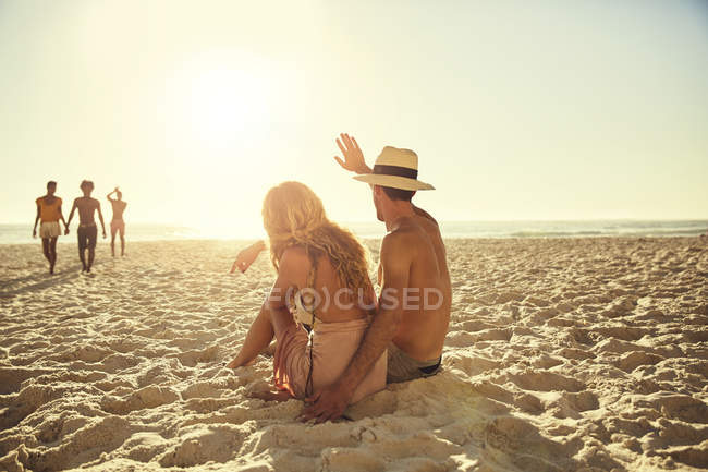 Young couple waving to friends on sunny summer beach — Stock Photo