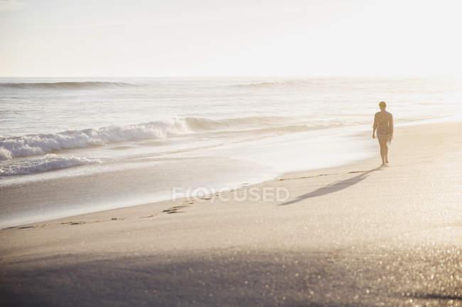 Silhouette Frau zu Fuß auf idyllische sonnige Sommerstrand — Stockfoto