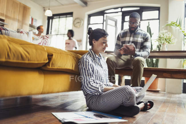 Female freelancer working at laptop on living room floor — Stock Photo