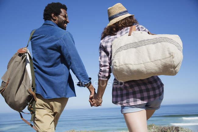 Multi-ethnic couple holding hands, walking on sunny summer ocean beach — Stock Photo