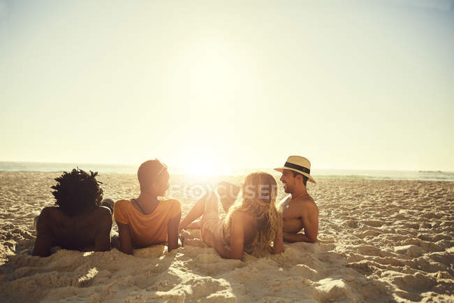 Young couples laying, relaxing on sunny summer beach — Stock Photo