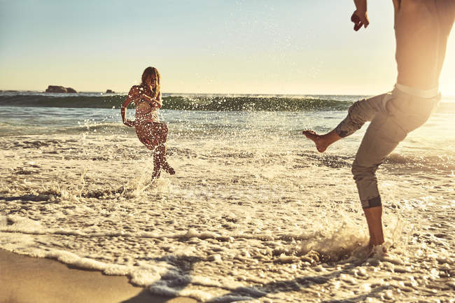 Playful young couple splashing in sunny summer ocean surf — Stock Photo