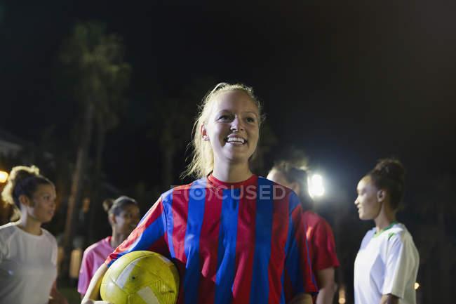 Ritratto sorridente, fiducioso giovane calciatore femminile con la sfera — Foto stock