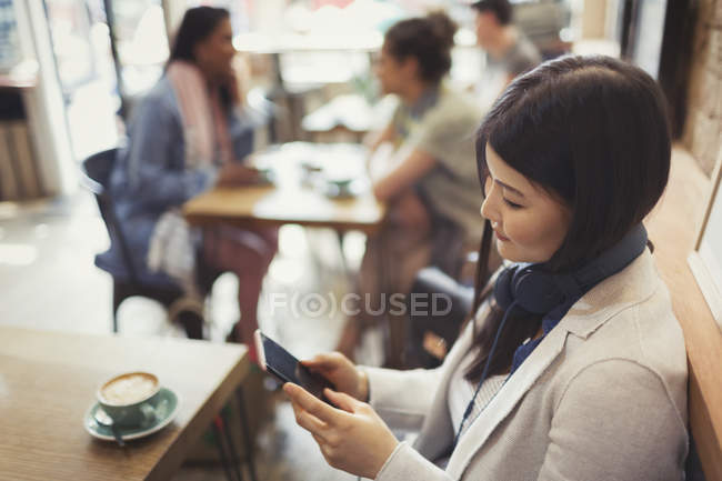 Jeune femme avec écouteurs textos avec téléphone portable et boire du café à la table de café — Photo de stock