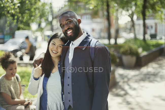 Portrait smiling, affectionate young couple hugging in sunny park — Stock Photo