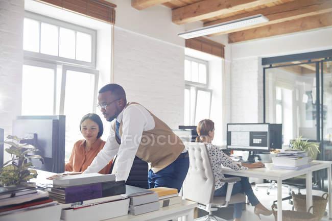 Бизнесмен и предпринимательница используют компьютер в офисе — стоковое фото