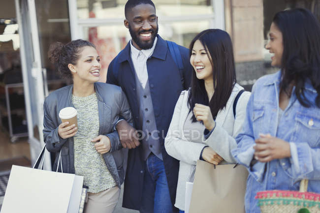 Smiling friends with coffee and shopping bags — Stock Photo