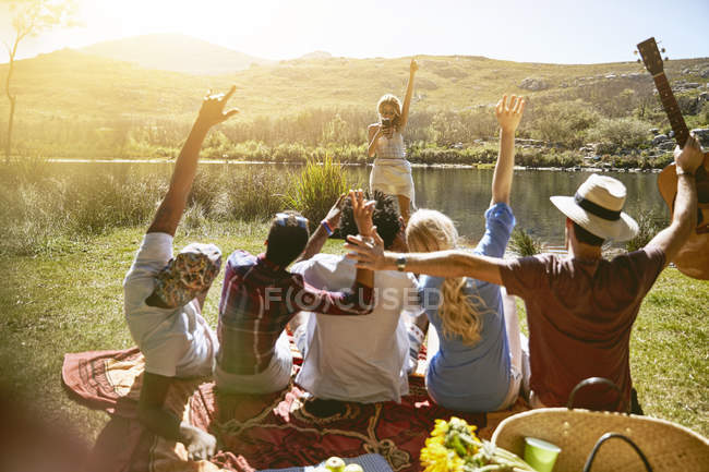 Woman with camera phone photographing friends with arms raised at sunny summer riverside — Stock Photo