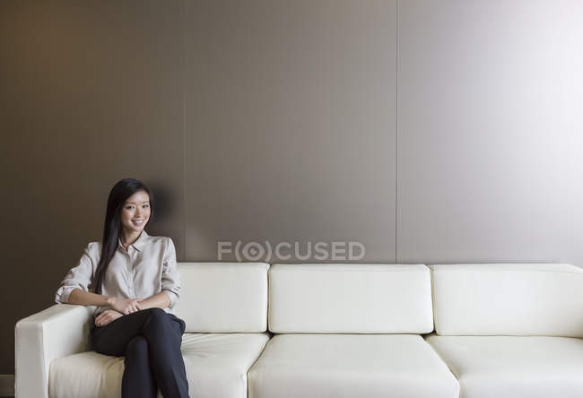 Portrait smiling businesswoman on sofa at modern office — Stock Photo