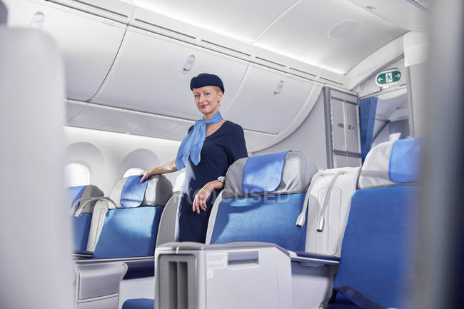 Retrato seguro mujer auxiliar de vuelo en avión - foto de stock