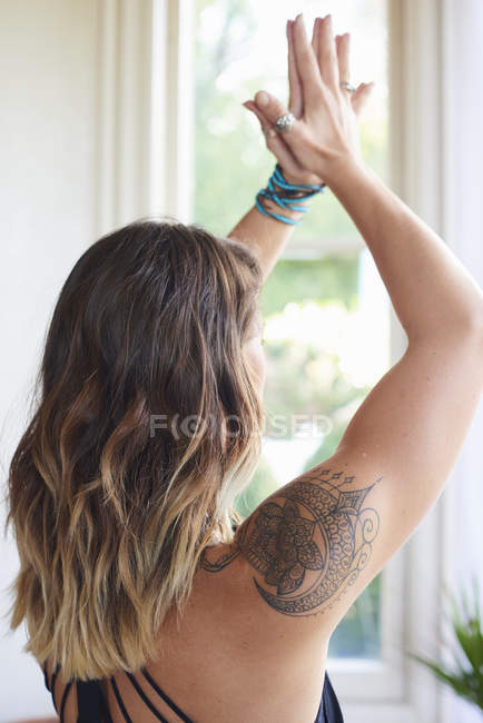 Serene woman with tattoo practicing yoga with hands clasped overhead — Stock Photo