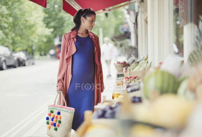 Femme enceinte shopping produits vitrine de marché — Photo de stock