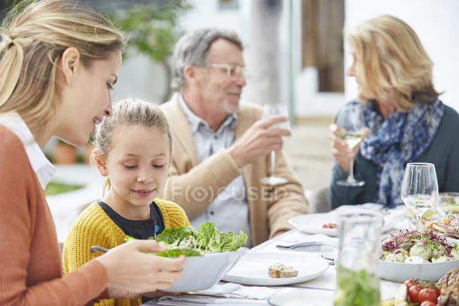 Семья из нескольких поколений наслаждается обедом в патио — стоковое фото