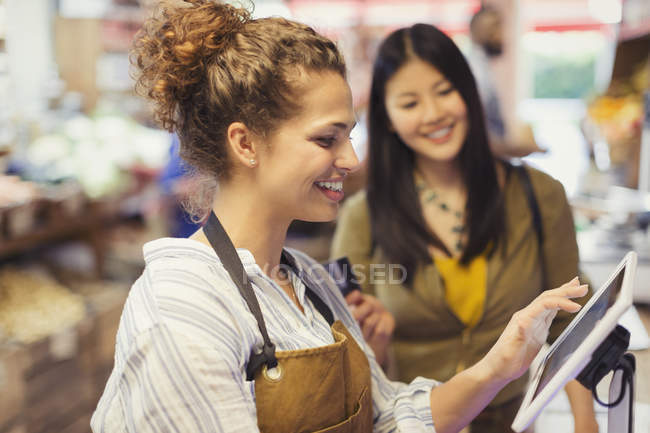 Female cashier helping customer at touch screen cash register in grocery store — Stock Photo