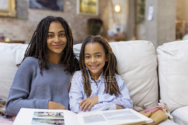 Портрет, посміхаючись, впевнено сестри з фотоальбом на дивані — стокове фото