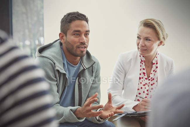 Young man talking in group therapy session — Stock Photo