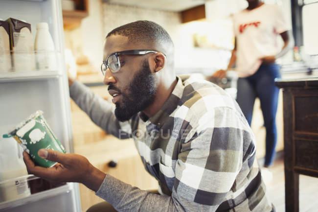 Молодой человек читает этикетку на контейнере в холодильнике — стоковое фото
