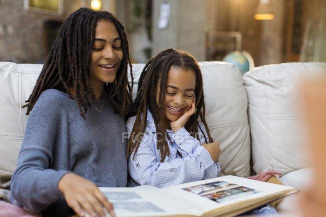 Усміхаючись сестри, дивлячись на фото альбом — стокове фото