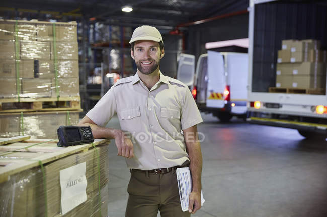 Portrait confident truck driver worker at distribution warehouse loading dock — Stock Photo