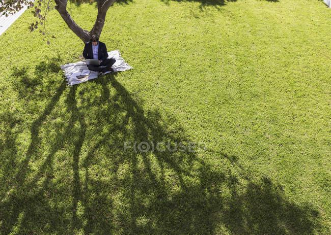 Businessman working, using laptop on blanket below tree in sunny yard — Stock Photo