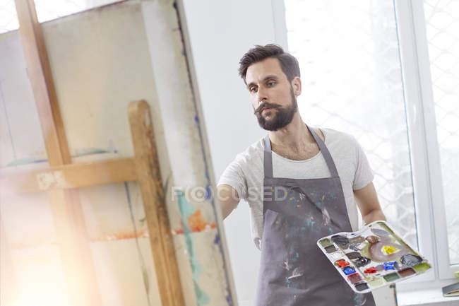 Male artist with palette painting at easel in art studio — Stock Photo