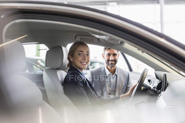 Ritratto donna sorridente e venditore di auto seduto in auto nuova in concessionaria auto — Foto stock