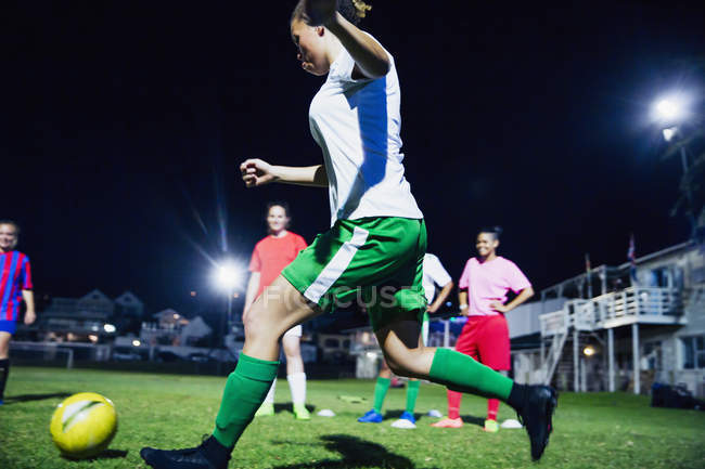 Junge Fußballspielerinnen, die nachts auf dem Feld Fußball spielen und den Ball kicken — Stockfoto