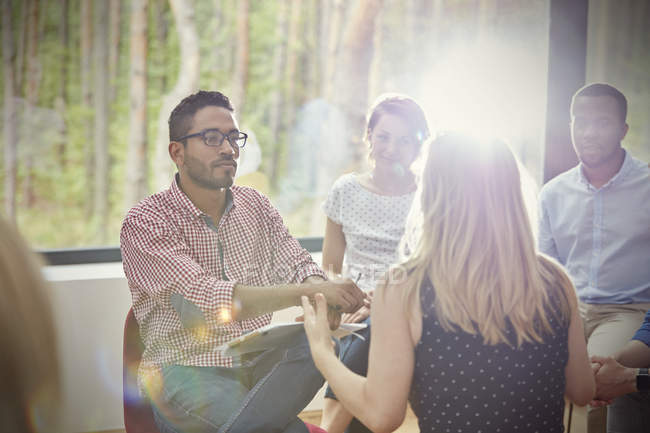 Attentive man listening to woman in group therapy session — Stock Photo